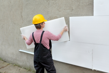 Female worker carry styrofoam sheet insulation at construction site