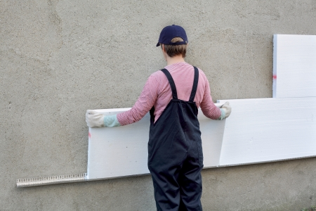 Female worker placing styrofoam sheet insulation to the wall Stockfoto