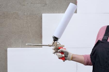 pegamento: Mano del trabajador celebración de poliuretano expansión pegamento de espuma aplicador arma
