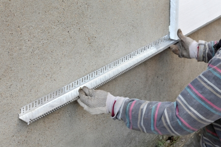 Worker placing aluminum batten for styrofoam sheet insulation to the wall Stockfoto