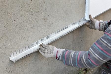 Worker placing aluminum batten for styrofoam sheet insulation to the wall Standard-Bild