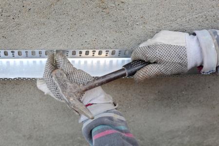 hand job: Worker placing aluminum batten for styrofoam sheet insulation to the wall Stock Photo