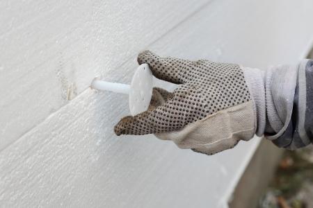 拡大: 労働者の壁の断熱発泡スチロール シートに拡張アンカーを配置します。