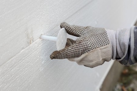 Worker placing expansion anchor to styrofoam sheet insulation of the wall Stockfoto