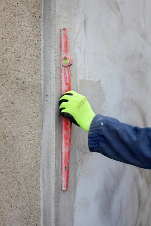 leveler: Worker control polystyrene insulation of wall with level tool
