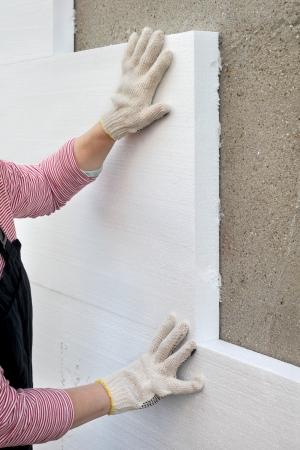 estuco: Trabajador colocando aislamiento l�mina de poliestireno para la pared Foto de archivo
