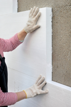 Worker placing polystyrene sheet insulation to the wall Stockfoto
