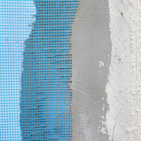 Closeup of layers over polystyrene insulation, mesh, plaster, cement, mortar