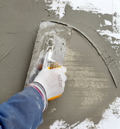 polystyrene: Worker spreading  mortar over polystyrene insulation with trowel