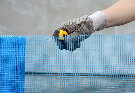 Close up of worker hands cut mesh for polystyrene insulation photo