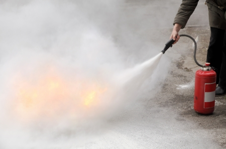 A woman demonstrating how to use a fire extinguisher Stock Photo