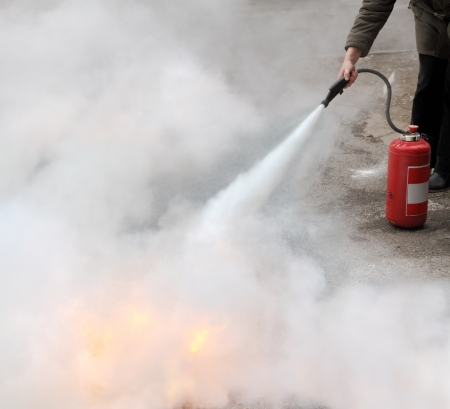 A woman demonstrating how to use a fire extinguisher Stockfoto