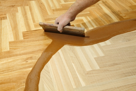 treated board: Varnishing of oak parquet floor, workers hand and tool Stock Photo