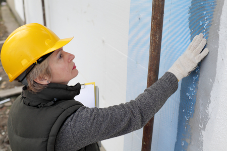 styrofoam: Construction inspector examine styrofoam insulation of house facade, wall