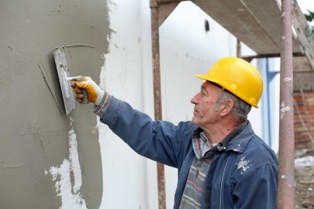 Worker spreading  mortar over styrofoam wall insulation with trowel Stockfoto