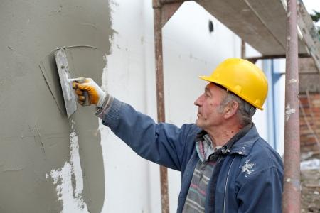 Worker spreading  mortar over styrofoam wall insulation with trowel Standard-Bild