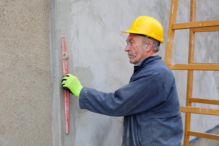 styrofoam: Worker control styrofoam insulation of wall with level tool