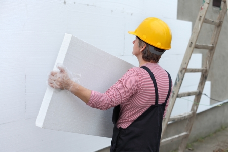 placing: Female worker carry styrofoam sheet insulation at construction site