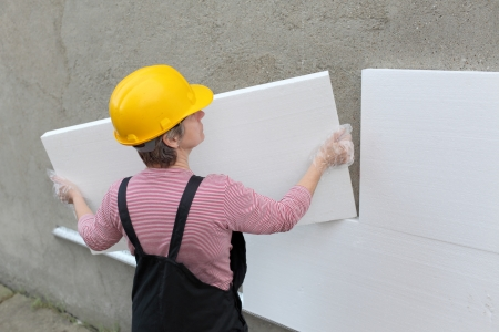 Female worker placing styrofoam sheet insulation to wall at construction site Stockfoto
