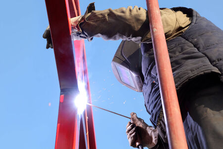 Worker welding metal tube construction with blue sky in background photo