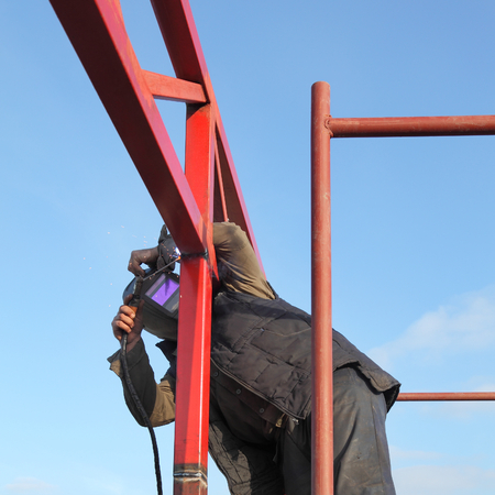 Worker welding metal tube construction with blue sky  photo