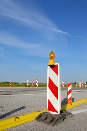 Roadworks, road sign in a highway on reconstruction with blue sky and clouds photo