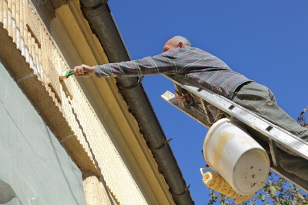 Senior worker at ladder painting old house facade photo