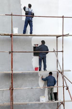 Los trabajadores en los andamios difusión estuco sobre el aislamiento del mortero y de la pared con una llana