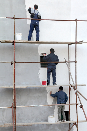 Workers at scaffolding spreading stucco over mortar and wall insulation with trowel