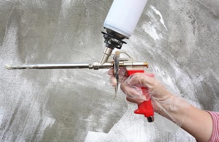 pegamento: Mano del trabajador celebraci�n de poliuretano expansi�n pegamento de espuma aplicador arma