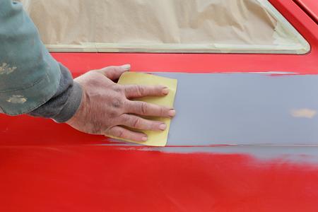 Car ready for repaint, worker sanding primer