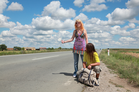 hitch hiker: Young people, Caucasian girl and boy  hiking at a road