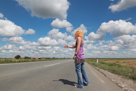 Young people, Caucasian girl hitch hiking at a road photo