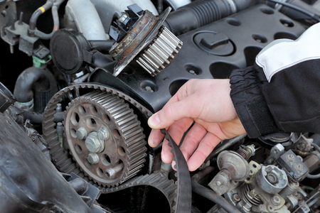 Car mechanic replacing timing belt at camshaft of modern engine photo