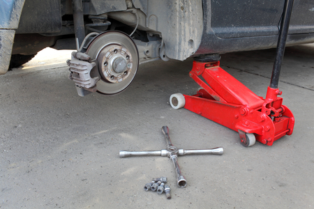 Car at hydraulic jack, disc brakes, screws and  lug wrench tool