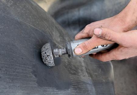 grinder machine: Worker using tire grinder machine for tire repairing