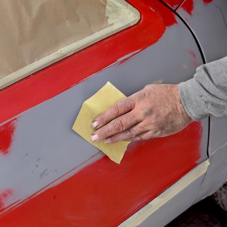 repaint: Car ready for repaint, worker sanding primer