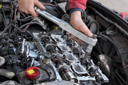 handtool: Mechanic fixing cylinder head with two camshaft of car engine with socket wrench