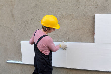 Female worker placing styrofoam sheet insulation to the wall photo
