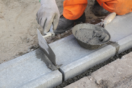 stone work: Worker installing curb stone, using trowel and mortar