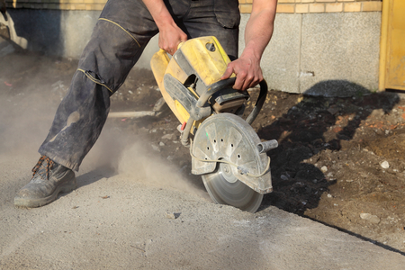 Asphalt or concrete cutting with saw blade at construction site