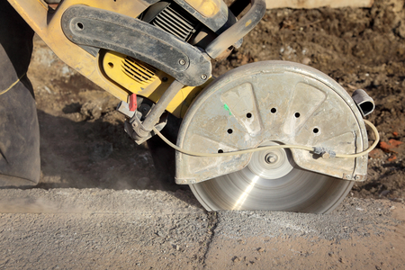 Asphalt or concrete cutting with saw blade at construction site photo
