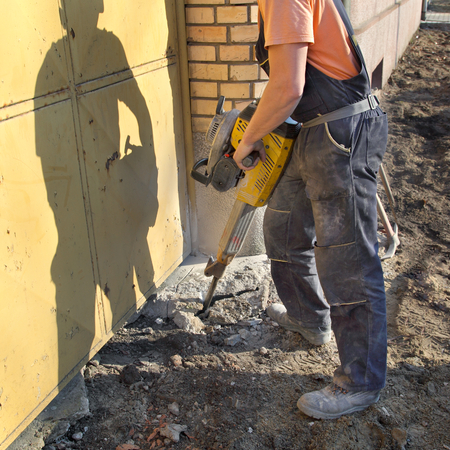 Worker  at site working with pneumatic plugger hammer Standard-Bild