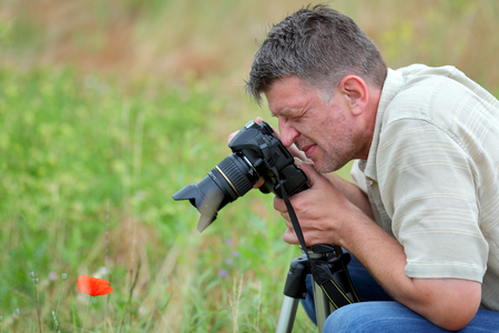 Photographer in nature taking picture of poppy at meadow photo