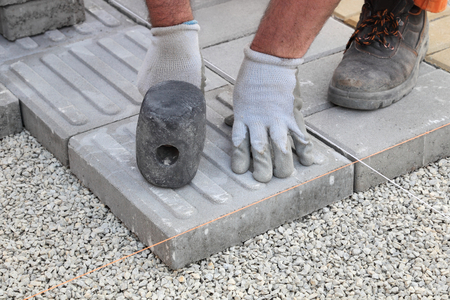 paving stone: Construction site, worker installing concrete brick pavement, using hammer Stock Photo
