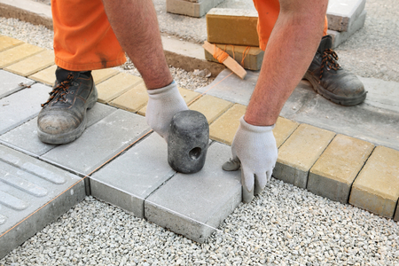 Construction site, worker installing concrete brick pavement, using hammer Stockfoto