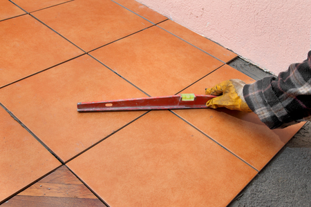 leveling: Home renovation, worker leveling tiles with level tool