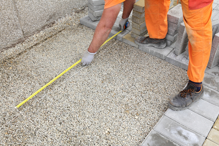 Construction site, worker measuring foundation of concrete brick pavement photo