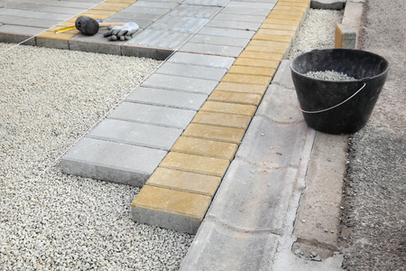 Installing of concrete brick pavement to gravel foundation photo