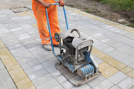 Worker finishing concrete brick pavement with vibratory plate compactor
